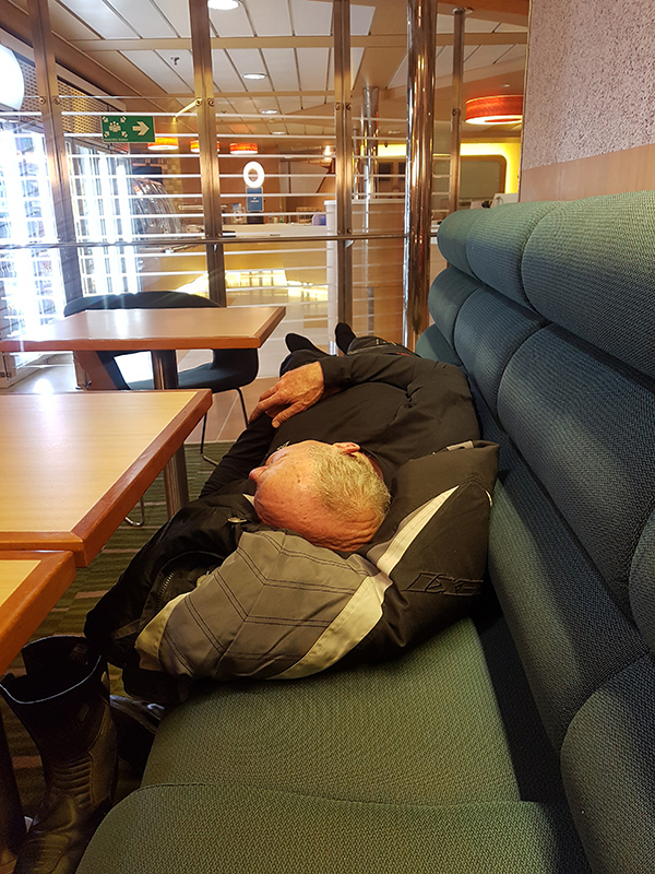 Bill sleeping on the ferry, the empty café in the distance